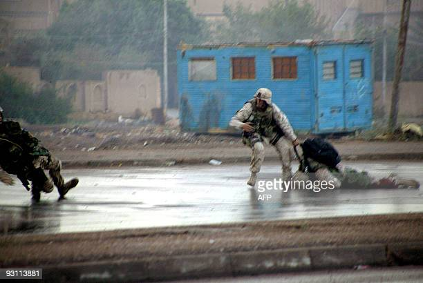A picture released by the US Marines 18 December 2004 shows Gunnery Sgt Ryan P Shane falling as he is hit by enemy fire as he and another member of...