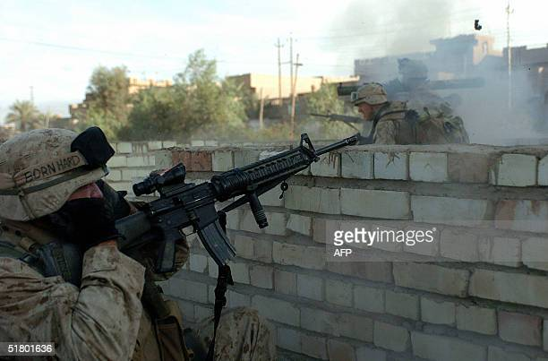 Picture released by the US Marines 29 November 2004 shows Cpl Gabriel Trull pluging his ears as Lance Cpl Evan Fernandez fires a round from his MK153...