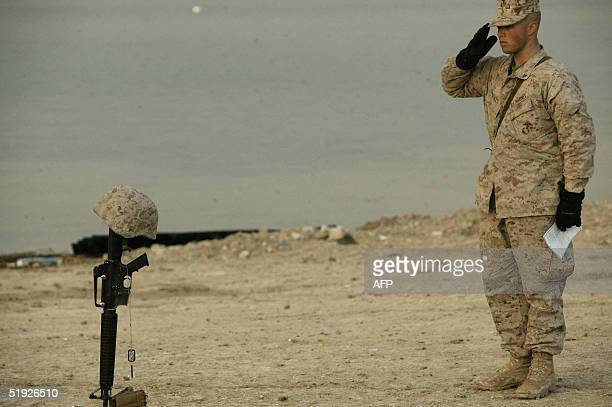 A picture released by the US Marines shows a Marine with the Small Craft Company mourning the memorial rifle Kevlar helmet dog tags and boots of...