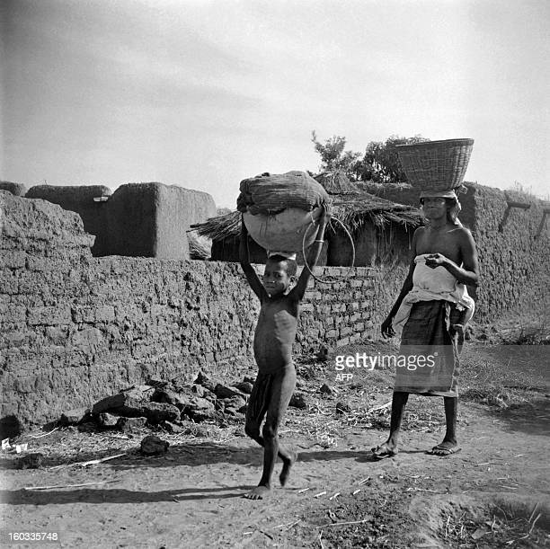 A picture released in 1951 shows Malians carrying goods on the head in a village near Bamako