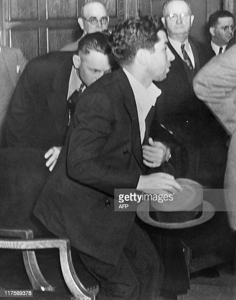 Picture released on April 8 1936 of alleged 'king in Arkansas' Charles 'Lucky' Luciano Italian gangster rising in front of deputy sheriffs during a...