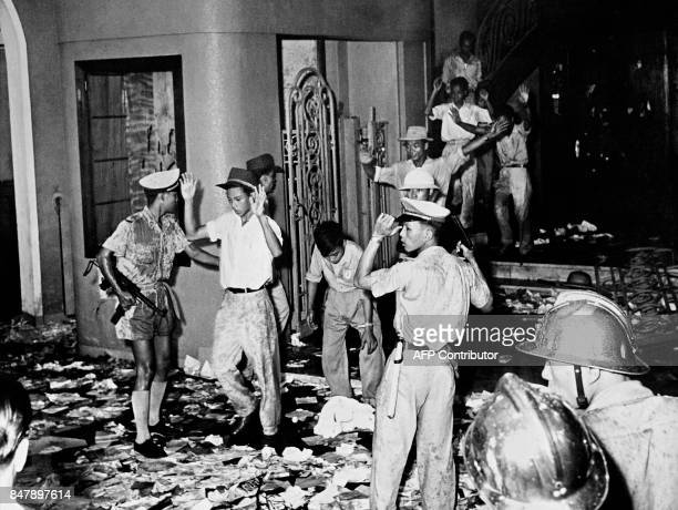 Picture released on July 22, 1964 in Saigon of policemen arresting protestors who wrecked the Majestic Hotel during a demonstration against the...