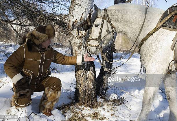 Picture released on March 6, 2010 shows Russian Prime Minister Vladimir Putin stroking a horse in the Karatash area, near the town of Abakan, during...