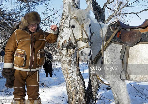 Picture released on March 6, 2010 shows Russian Prime Minister Vladimir Putin looking at a horse in the Karatash area, near the town of Abakan,...