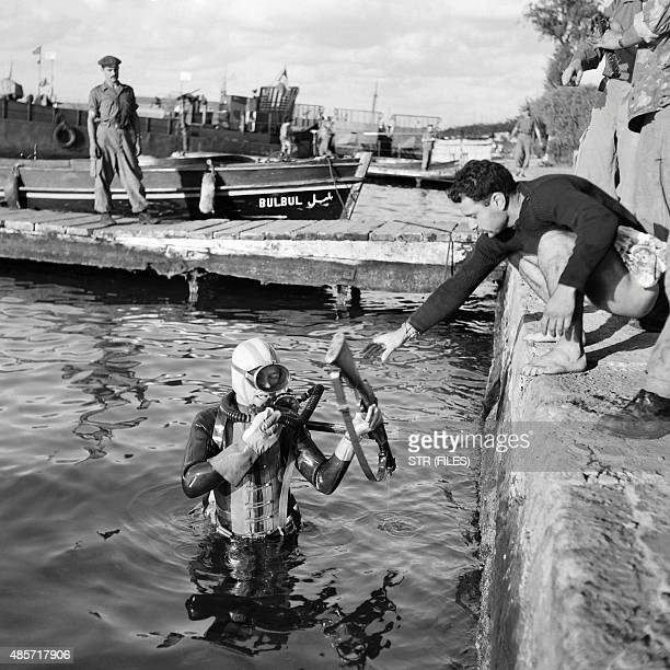Picture released on November 1956 of French divers pulling out arms from the Suez Canal, in Port Saïd, in Egypt after the Suez crisis. / AFP / STR