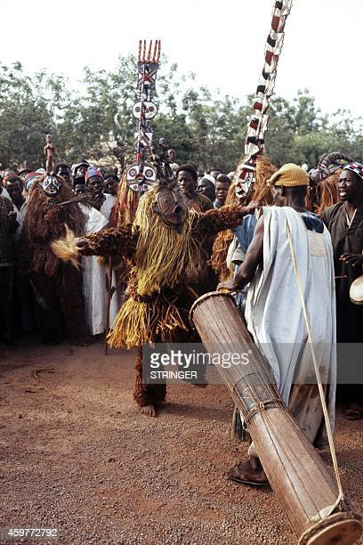 Picture released on November 1972 in Ouagadougou of Burkinabe dancers and musiciens wearing traditional masks during French President Georges...