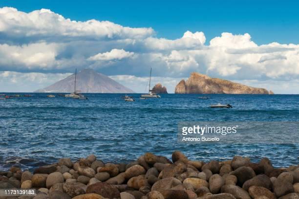 picture rocks called lisca bianca off the island of panarea with stromboli volcano in the background - äolische inseln stock-fotos und bilder