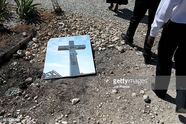 Picture showing a cross next to a church destroyed during the earthquake lays on the ground as people place flowers and pay their respects at a...