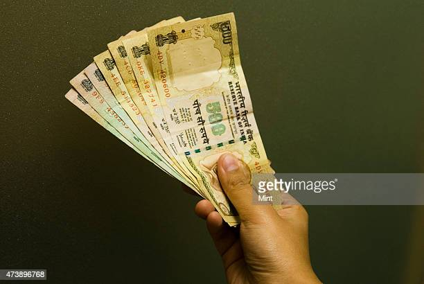 Picture showing hand holding the currency notes of Indian 100 and 500 Rupees in New Delhi India