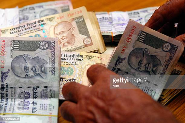 Picture showing hands counting the currency notes of Indian one hundred rupees in New Delhi India