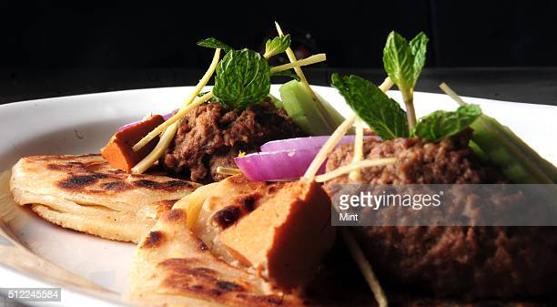 Picture showing special Lucknowi Bengali dish named Ghutwan Kabab with Paratha served with ginger juliennes cucumber onion and smoked bandel Cheese...