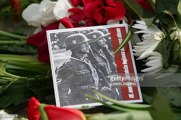 A picture showing SS soldiers is layed on flowers at the Freedom monument 16 March 2005 in Riga during Legion Day which commemorates Latvians who...