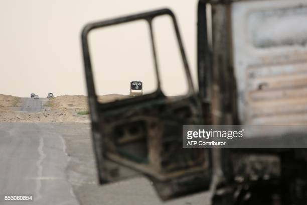 A picture shows a billboard bearing the logo of the Islamic State group through the wreckage of a truck on the outskirts of Deir Ezzor on September...
