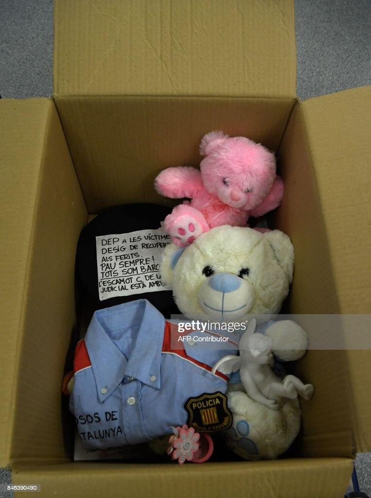 Picture shows a box with teddy bears and a police uniform collected at Las Ramblas makeshift memorial, set up following the August, 17 Barcelona jihadist attack, and stored to be catalogued and preserved at the Museu D'Historia de Barcelona (MUHBA) on September 13, 2017 in Barcelona. /