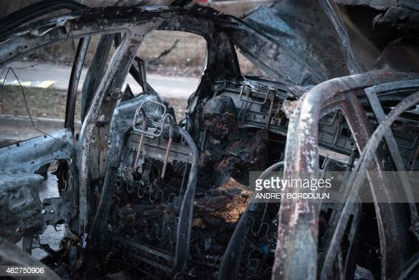 A picture shows a burnt body sitting inside a destroyed car after shelling in Donetsk eastern Ukrane on February 4 2015 At least 12 people were...