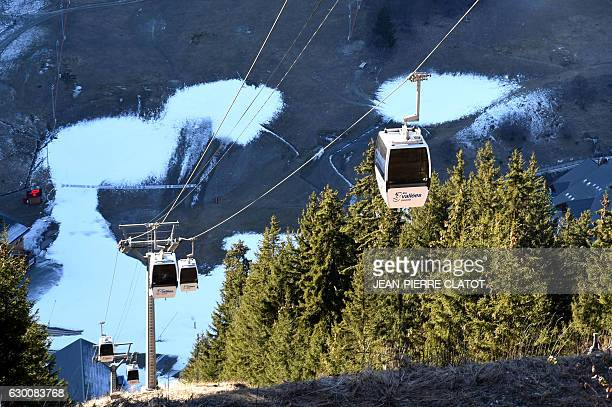 A picture shows a cable car and slopes where snow is sparse in the French ski resort of Meribel French Alps on December 16 on the eve of Christmas...