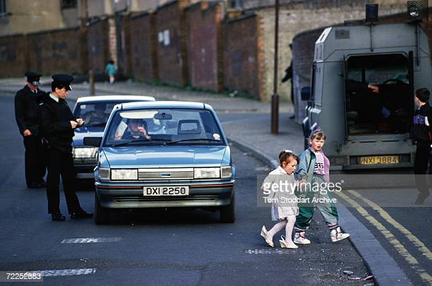 Picture shows a child wearing her mother's shoes beside policemen from the Royal Ulster Constabulary at a checkpoint in Belfast during the troubles