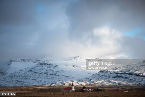 A picture shows a church near a snowcovered hill on April 12 2017 in the Nordurland eystra region of Iceland / AFP PHOTO / LOIC VENANCE