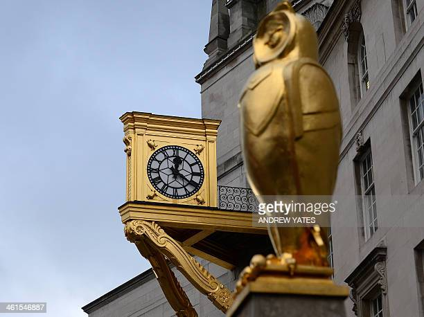 A picture shows a clock tower and the guilded owl sculpture on the front of Leeds Civic Hall in Leeds northwest England on January 9 2014 The Grade...