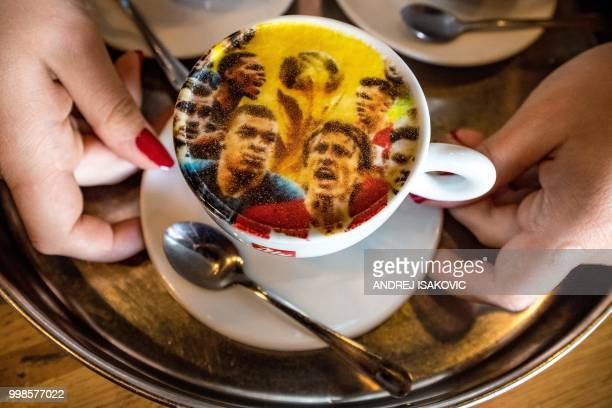 TOPSHOT A picture shows a coffee cup covered by a printed image displaying Croatian and French national football teams in Zagreb on July 14 ahead of...