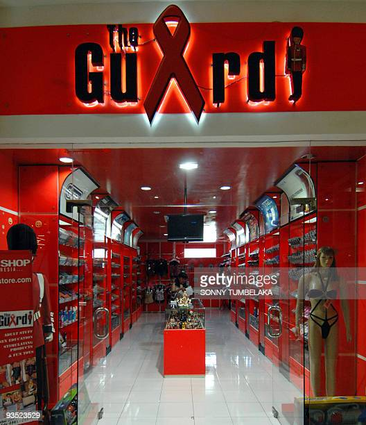 A picture shows a condom and sextoy shop in Kuta on the resort island of Bali using the red ribbon symbol of AIDS prevention in its signage on...