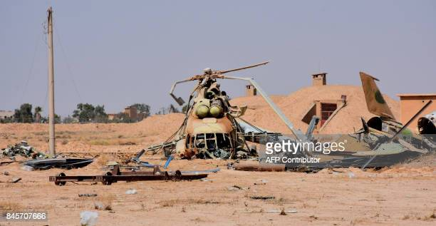 A picture shows a destroyed army helicopter at the military airport in the eastern Syrian city of Deir Ezzor on September 11 as Syrian government...