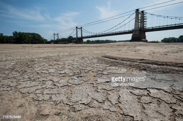 A picture shows a dry part of the bed of the River Loire at MontjeansurLoire western France on July 24 as drought conditions prevail over much of...