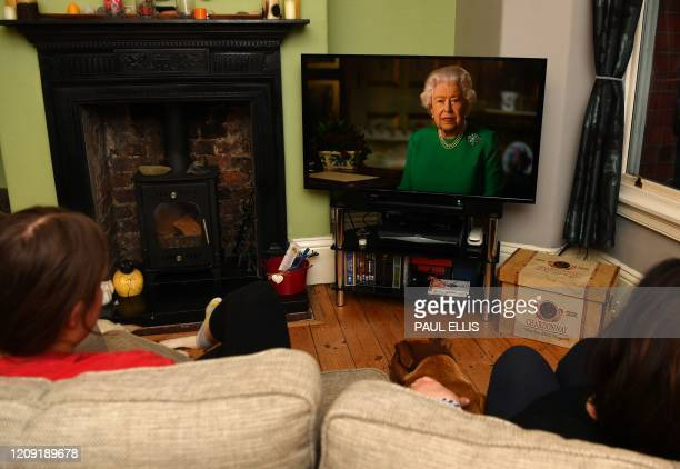 TOPSHOT A picture shows a family in Birkenhead northwest England on April 5 2020 watching Britain's Queen Elizabeth II deliver a special address to...