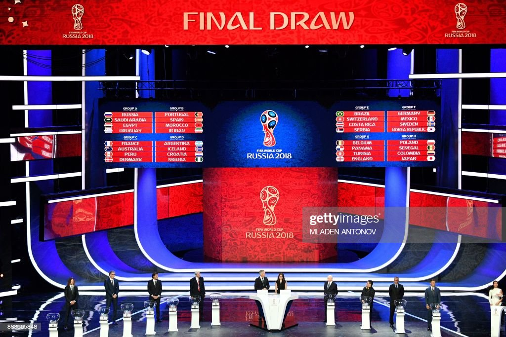 TOPSHOT - A picture shows a general view with the groups displayed on screens after the Final Draw for the 2018 FIFA World Cup football tournament at the State Kremlin Palace in Moscow on December 1, 2017. The 2018 FIFA World Cup will be held from June 14 and July 15, 2018, in 11 Russian cities. / AFP PHOTO / Mladen ANTONOV