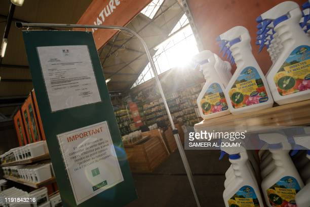 A picture shows a governmental agreement note next to organic insecticide bottles displayed for sale at a garden store on December 30 2019 in the...