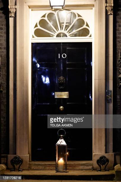 Picture shows a lit candle on the step of the official residence of Prime Minister Boris Johnson at 10 Downing Street in London on March 13, 2021...