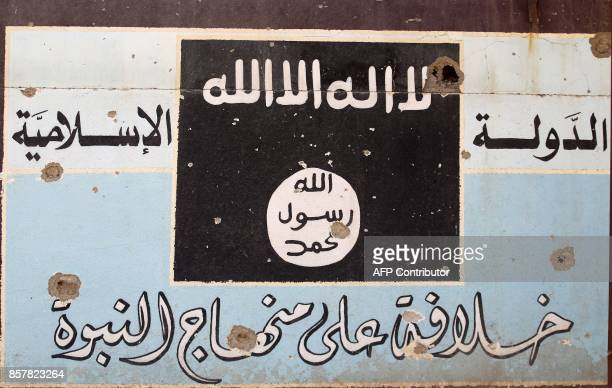 A picture shows a mural depicting the emblem of the Islamic State group as Iraqi forces backed by fighters from the Hashed alShaabi advance through...