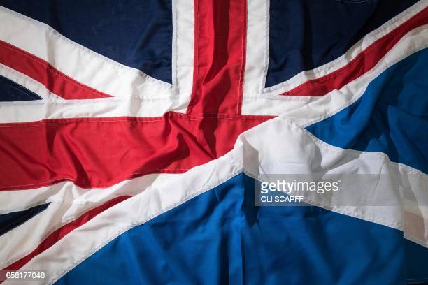 A picture shows a pair of flags arranged as an illustration a Saltire the national flag of Scotland and a Union Flag at the factory of 'Flagmakers'...
