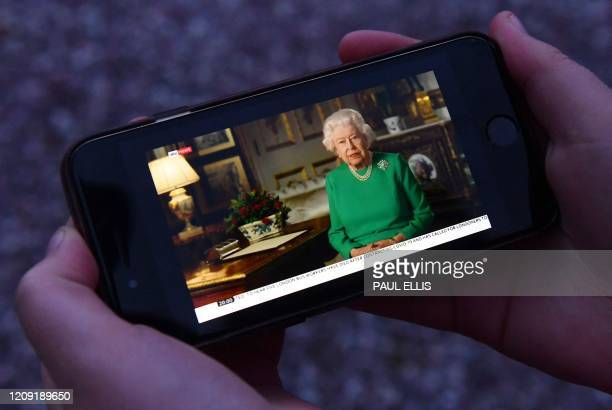 Picture shows a person in Birkenhead, northwest England on April 5, 2020 posing holding a smartphone showing Britain's Queen Elizabeth II deliver a...
