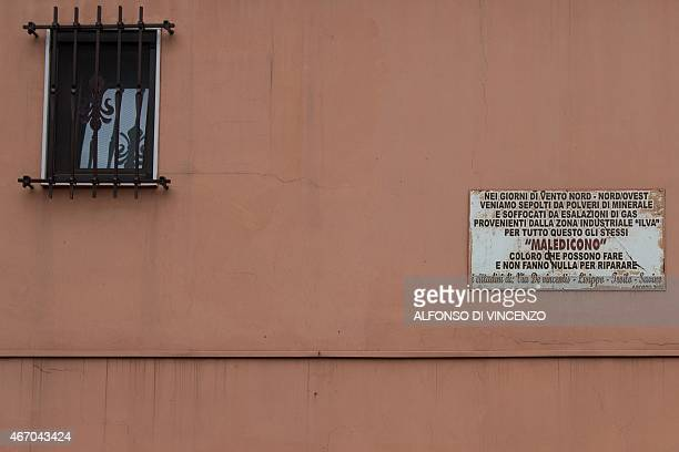 IDE A picture shows a plaque to denounce inaction against pollution coming from the Ilva steel plant in the Tamburi district of Taranto on March 18...