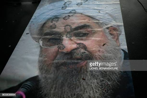 TOPSHOT A picture shows a portrait of Iranian President Hassan Rouhani with shoe marks over it during a demonstration in support of the Iranian...