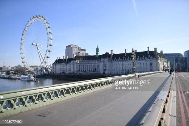 A picture shows a quiet Westminster Bridge with the London Eye in the background in central London in the morning on March 24 2020 after Britain...