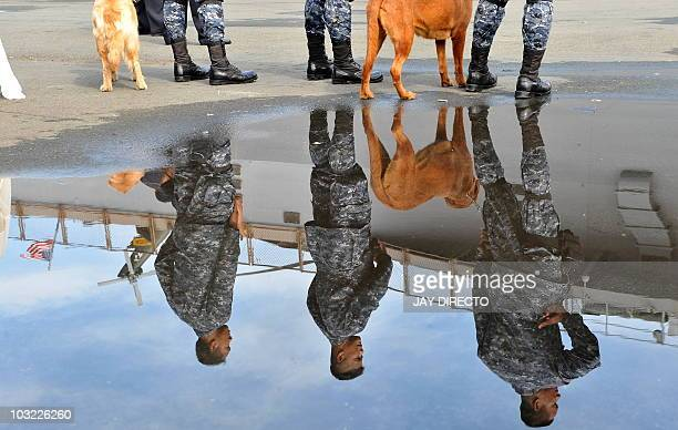 A picture shows a reflection of Philippine Coast Guards securing the port as the USS Blue Ridge the flagship of the US Navy Seventh Fleet arrives at...