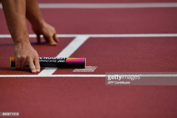 TOPSHOT A picture shows a runner holding a baton at the start of the men's 4x100m relay athletics event at the 2017 IAAF World Championships at the...