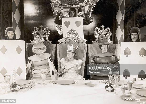 1933 Picture shows a scene from the movie Alice in Wonderland written by Lewis Carroll Alice is shown seated between the two chess pieces in a chair...