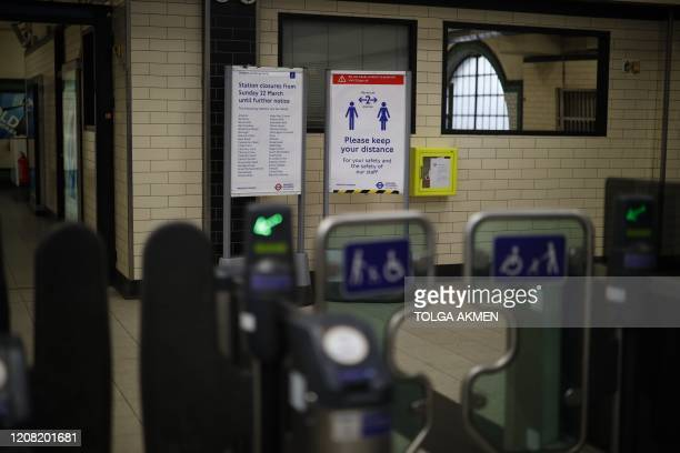 A picture shows a sign calling on passengers to observe social distancing in a London Underground tube station in London on March 25 after Britain's...