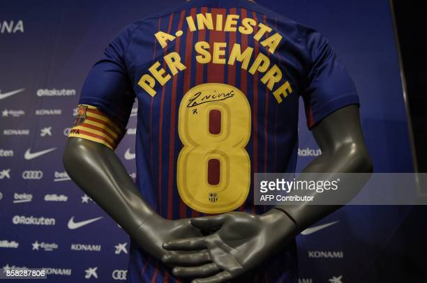 A picture shows a special FC Barcelona jersey signed by midfielder Andres Iniesta after he renewed his contract at the Camp Nou in Barcelona on...
