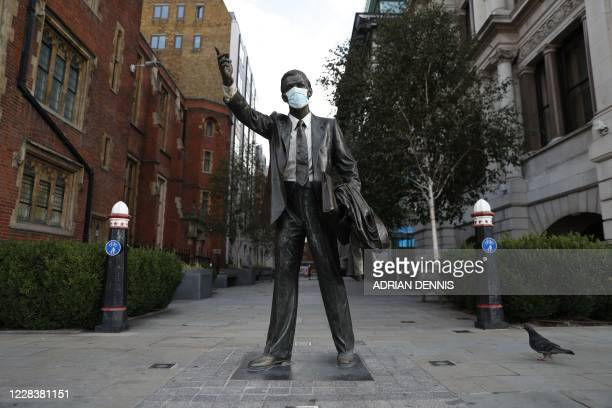 A picture shows a statue entiteld 'Taxi' by J Seward Johnson Jr with a facemask on it in the City of London on September 7 2020 Prime Minister Boris...