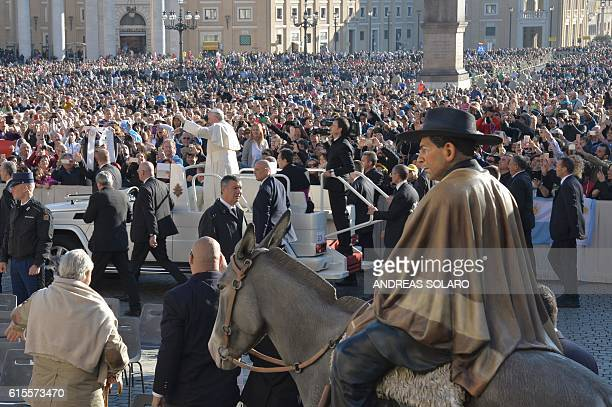 A picture shows a statue of 'gaucho priest' Saint Jose Gabriel del Rosario Brochero as Pope Francis waves to the crowd from the popemobile during his...