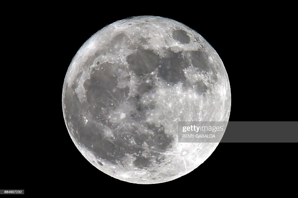 A picture shows a 'supermoon', seen from Trebons-sur-la-Grasse, southern France, on December 3, 2017. The lunar phenomenon occurs when a full moon is at its closest point to earth. /