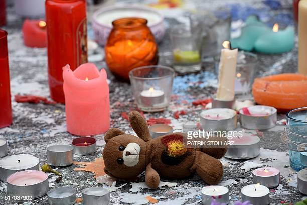 A picture shows a teddy bear layed next to candles as people gather to observe a minute of silence in memory of the victims of the Brussels airport...