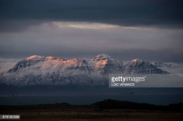 A picture shows a village near a snowcovered mountain on April 12 2017 in the Austurland region in Iceland / AFP PHOTO / LOIC VENANCE