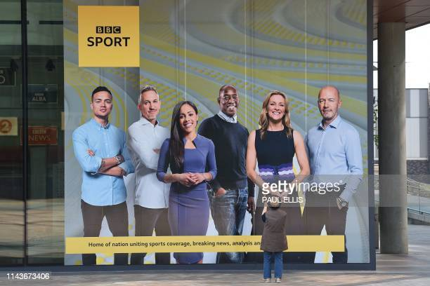 Picture shows a visitor taking a photograph of a large poster showing the BBC Sport presenters and pundits Jermaine Jenas, Gary Lineker, Alex Scott,...