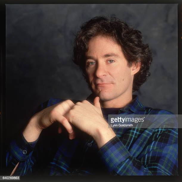 1989 Picture shows actor/comedian Kevin Kline seated with his hands in front of his chest wearing a blue and black check shirt
