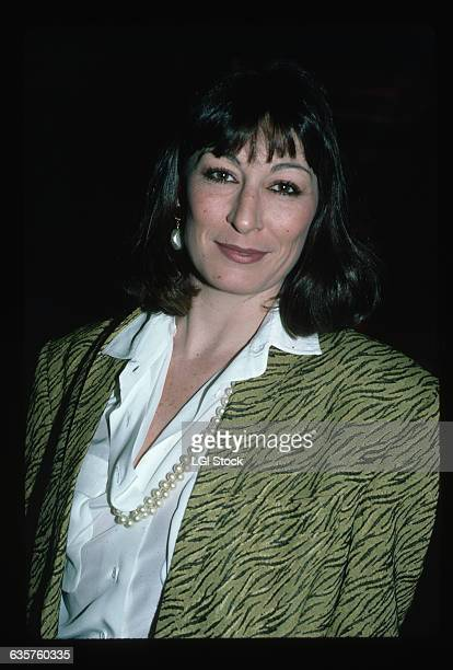 Picture shows actress, Anjelica Huston, posing for photographers wearing a black and green jacket, a white button-down and pearls.